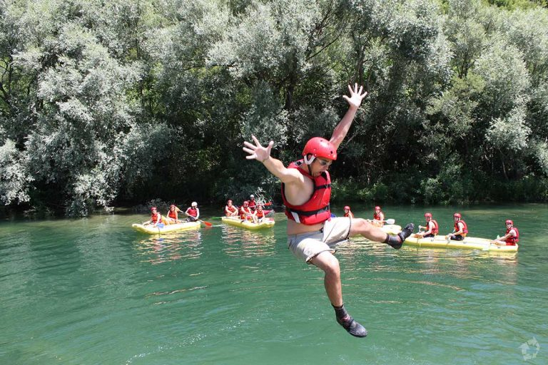 Jumping into refreshing Cetina river on rafting tour from Split