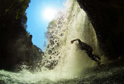 Jump through the waterfall into clear lake of Cetina